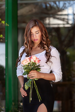 Young sensual woman with a bouquet of roses in hand