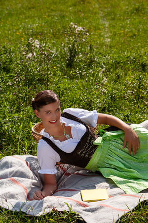 Portrait a smiling young woman in dirndl lying on the lawn Фото со стока