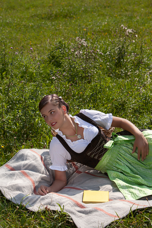 young bavarian woman in dirndl lies on a blanket in a mountain meadow Stock Photo