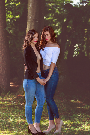 Full body shot of two women standing in front of a tree