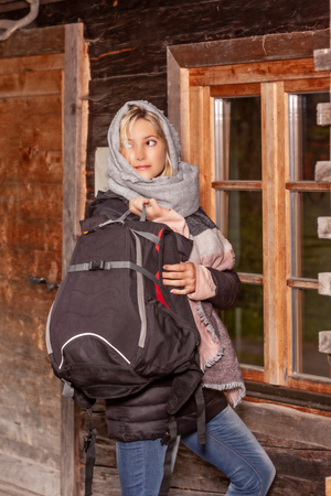 Portrait of a laughing young woman with backpack in winter