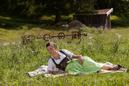 Young woman is lying on a meadow at a picnic in dirndl