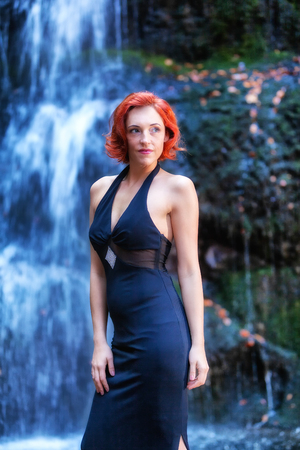 Portrait of young caucasian red-haired woman standing in an evening dress in front of a waterfall.
