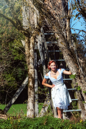 Portrait of a red-haired, smiling woman in dirndl, standing in a forest.