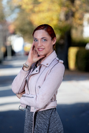 Portrait of a smiling young woman with red hair who is standing on the street
