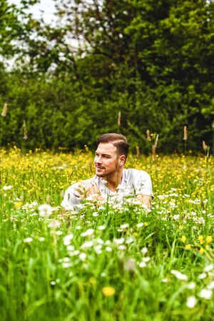Young man sits in a tall flower field