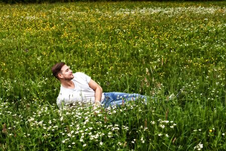 Young man with beard reads in a mountain meadow and enjoys the scent of flowers.