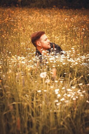 Young man with leather jacket lying in a meadow and looking into the distance.