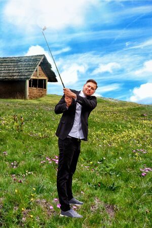 Man in business suit, standing on a mountain meadow with golf club
