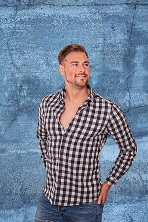 Attractive bearded man in a checked white shirt and jeans standing with his hands in his back pockets looking aside with a smile over a textured studio background Stock Photo