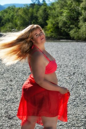 Attractive plus size woman in colorful red outfit posing outdoors on a pebbly beach with her blond hair blowing in the breeze looking back at the camera