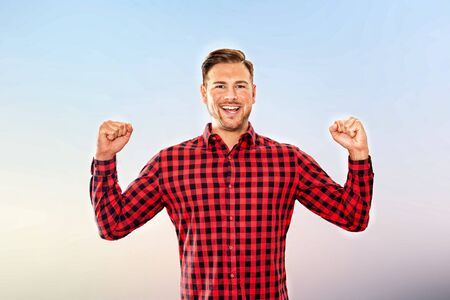 Exultant man cheering a personal success laughing and pumping the air with both fists in an upper body frontal view over sky