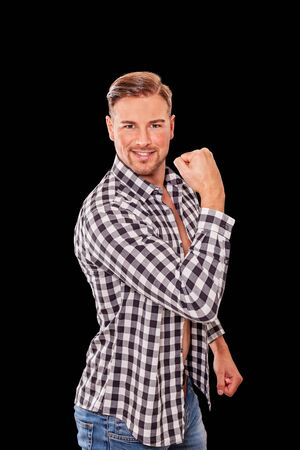 Attractive macho man flexing his arm muscles showing off his biceps in an unbuttoned black and white checked shirt while smiling at the camera.
