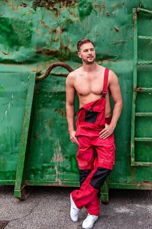 Muscular young man leaning against an old green container in a red dungarees.