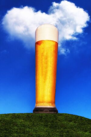 Wheat beer glass stands on a green meadow and rises into the blue sky with a cloud in heart shape. Stock fotó