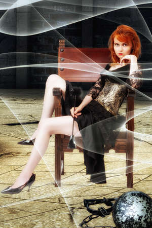 Red-headed girl sits in a black / gold corsage dress on a noble Spanish chair in a basement with sex toys in her hand