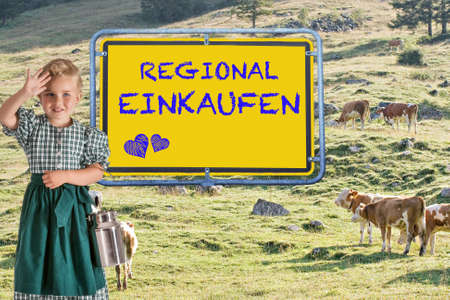 A small child in a dirndl with a milk jug in her hand in front of an alpine meadow with cows and the sign