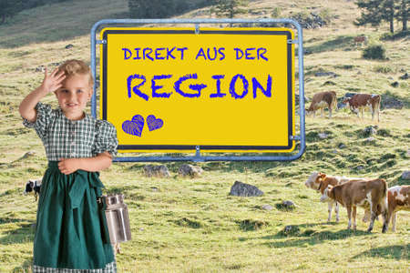 Little child in a dirndl with a milk jug in her hand in front of an alpine meadow with cows and the sign