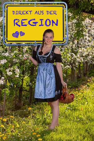 Young woman in dirndl with a basket of red apples in front of a sign with German inscription