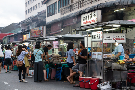 People wandering around the street in George Town, Penang, Malaysia in search for the best street food for their dinner.