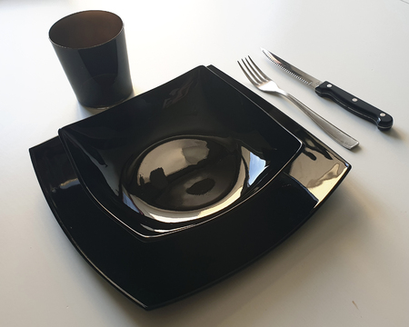 Black table set composed by black dishes, silver fork and black knife on white table Standard-Bild - 116018369