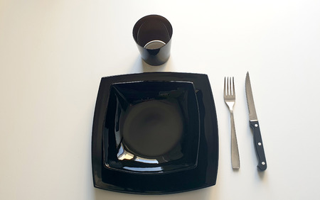 Black table set composed by black dishes, silver fork and black knife on white table