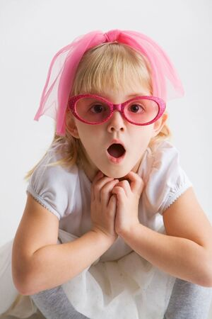 Little girl with pink glasses with a surprised expression 写真素材