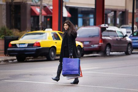 Girl with bags crossing the street 写真素材