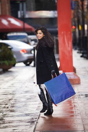 Women with shopping bags looking over shoulder