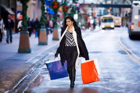 Girl with shopping bags walking down the street
