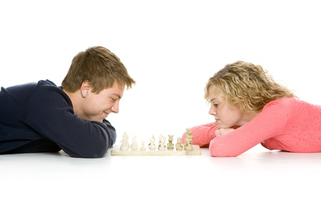 Attractive teenagers lying down playing chess photo