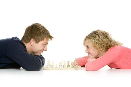 Attractive teenagers lying down using playing chess, isolated on white