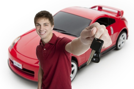 learner: Attractive teenage boy holding car keys with sports car in the background