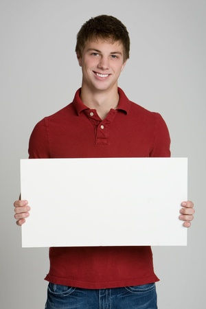 Attractive teenage boy holding a blank sign isolated on white background