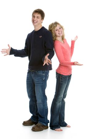 Attractive happy teenage couple standing back to back in studio with white background photo