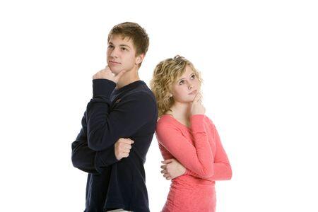 personnes de dos: Couple teenage attrayant commandes dos � dos pens�e en studio avec fond blanc