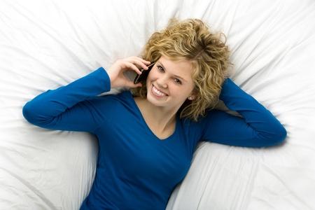 携帯電話で話している横になって美しい十代の少女 写真素材 - 8606323