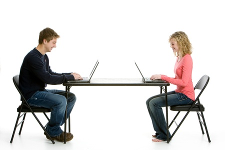 Teenage students on computers with white background in studio