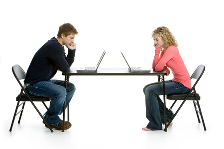 Attractive Teenage students using laptops on white background in studio photo