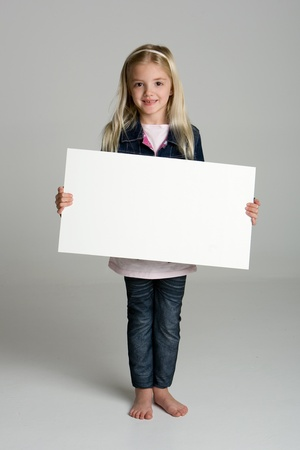 Happy little girl isolated on neutral background holding a blank sign