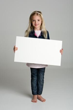 ni�os sosteniendo un cartel: Ni�a feliz aislada en fondo neutro, sosteniendo un signo en blanco Foto de archivo