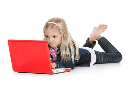 Cute little girl lying down with laptop staring at screen
