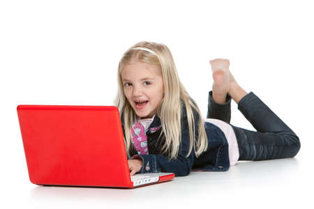 Cute little girl lying down with laptop laughing