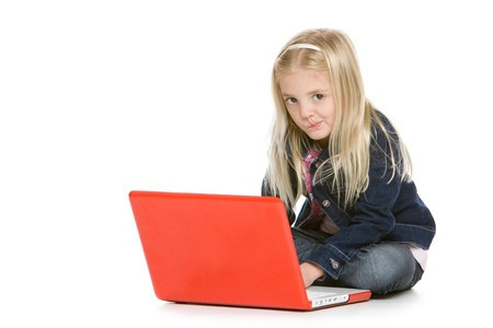 Cute little girl sitting down with laptop