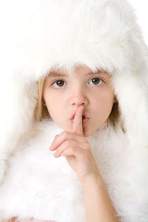 cute little girl wearing a white fur coat and hat, making a  photo