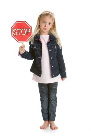 Cute little girl isolated on a white background holding a stop sign, with a sad face Stockfoto