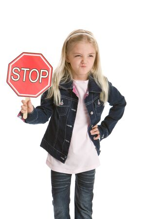 Cute little girl isolated on a white background holding a stop sign, smirking photo