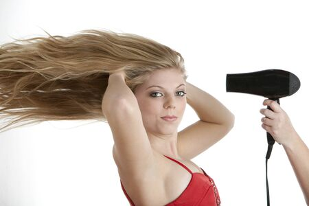 Beautiful blond teenage girl having her hair blow dried on isolated white background photo