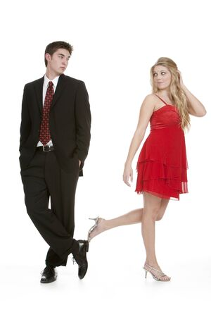 Attractive teenage girl in a red dress walking away from teenage boy in a suit isolated on white background photo