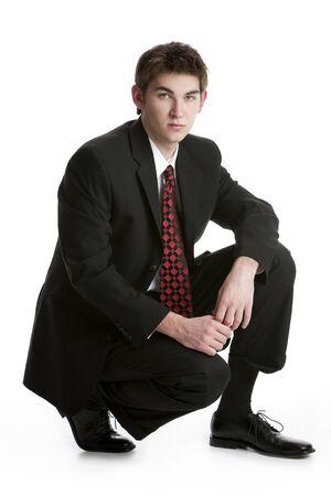 Attraktive Teenager kniend in einem Anzug isolated on white background